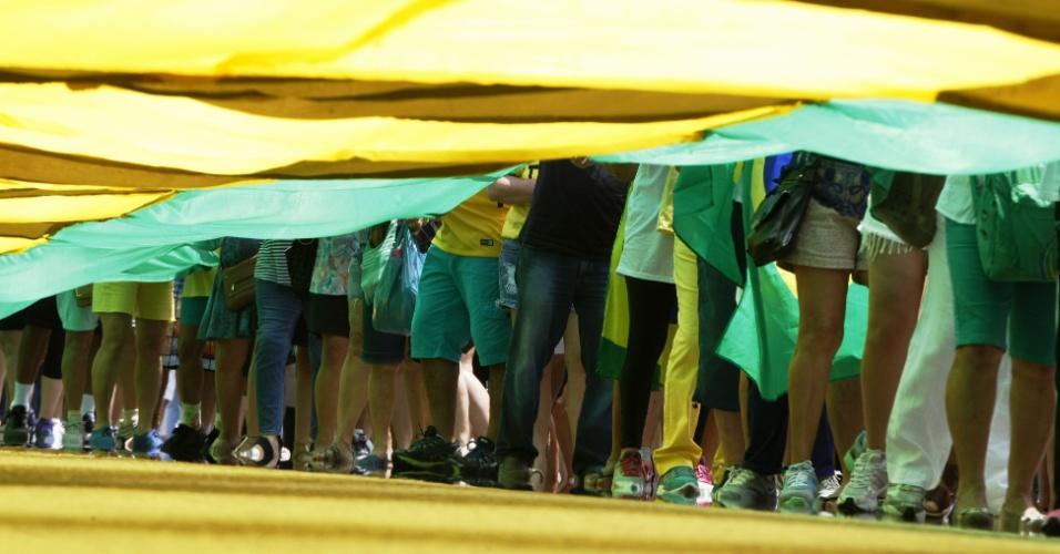 13.dez.2015 - Manifestantes vestindo camisas verde e amarela levam faixas e cartazes para protestar contra o governo da presidente Dilma Rousseff, na Avenida Atlântica, na cidade do Rio de Janeiro