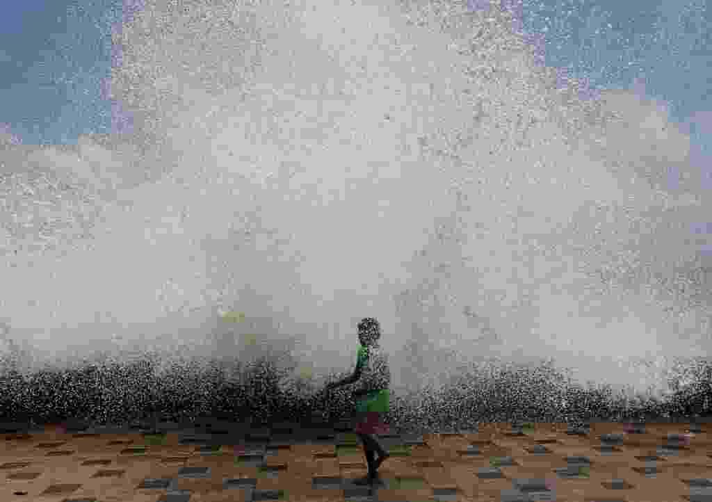 24.mai.2016 - Uma criança fica encharcada ao passar na frente de uma forte onda em Bombaim, na Índia - Siddiqui Danish/ Reuters