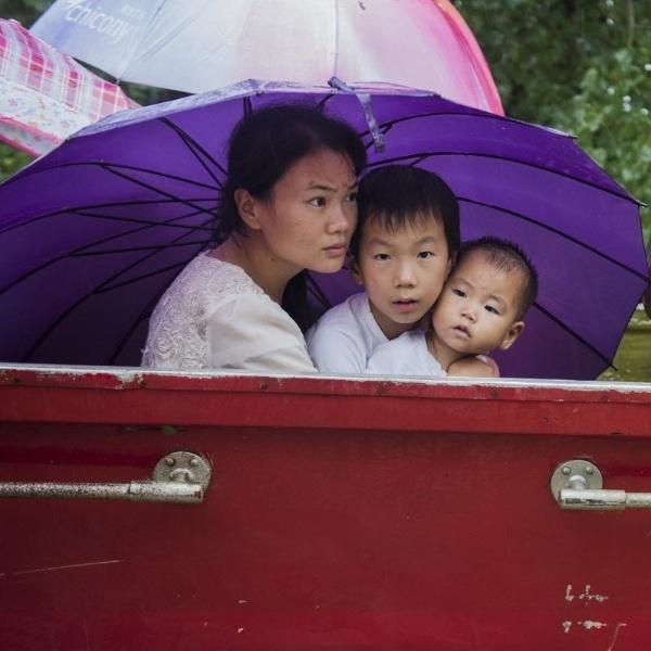 4.ago.2016 - Uma aldeã é transferida com os filhos para um lugar seguro em Wuhan, na província do Hubei, na China. As chuvas torrenciais atingiram as regiões sul e norte do país deixaram diversas cidades inundadas