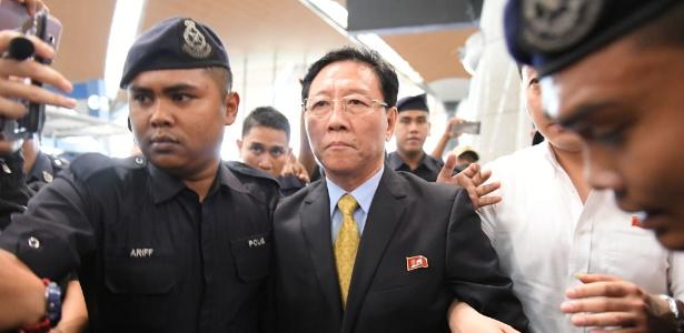 O embaixador norte-coreano Kang Chol (centro) é escoltado por policiais no terminal de embarque do aeroporto internacional de Kuala Lumpur, Malásia