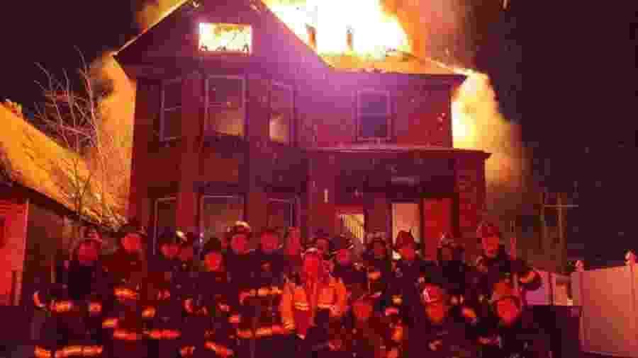 Bombeiros de Detroit, nos EUA, posaram em frente a uma casa em chamas às vésperas do Ano Novo; foto foi divulgada em redes sociais - Reprodução/WXYZ TV