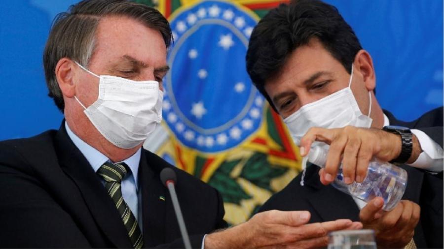 Luiz Henrique Mandetta joga álcool gel na mão de Jair Bolsonaro durante entrevista coletiva - Foto: Adriano Machado