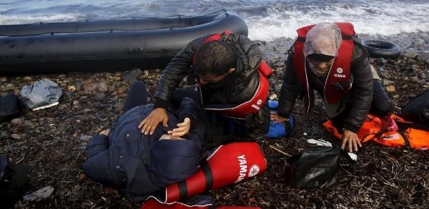 Refugiados sírios se deitam em terra firme, após cruzar o mar e chegar na ilha grega de Lesbos neste domingo - Yannis Behrakis/Reuters