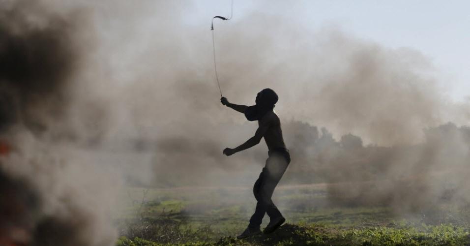 13.nov.2015 - Um manifestante palestino usa um estilingue para arremessar pedras em soldados israelenses durante confrontos perto da fronteira entre Israel e a faixa de Gaza