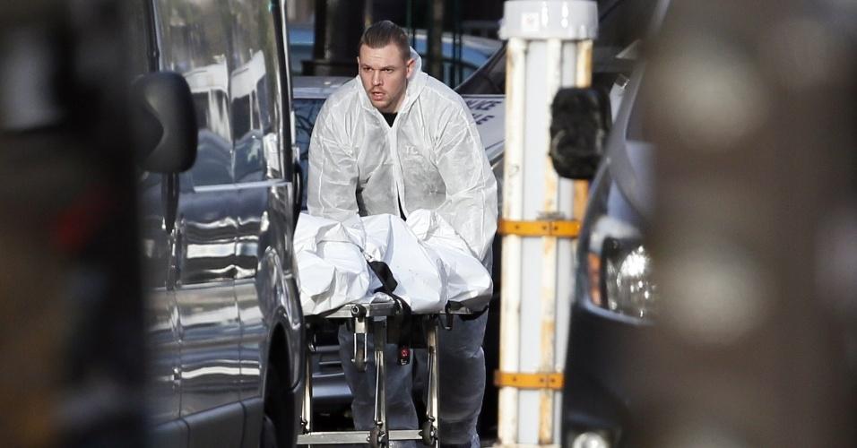 14.nov.2015 - Homem transporta corpo na manhã deste sábado (14), próximo ao Bataclan, local de shows que sofreu o ataque mais grave na noite anterior, em Paris