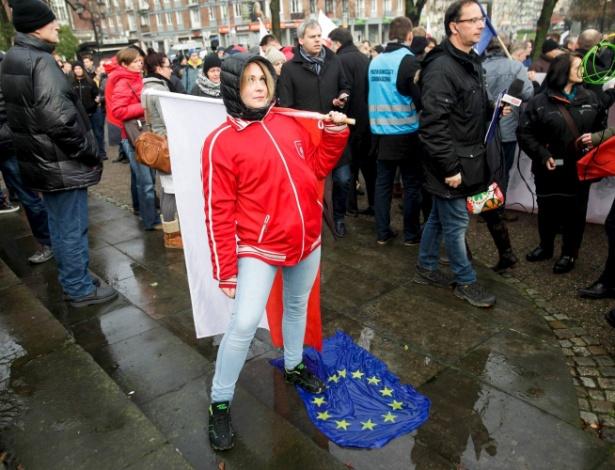 Mulher pisa em bandeira da União Europeia durante protesto contra imigrantes na Polônia