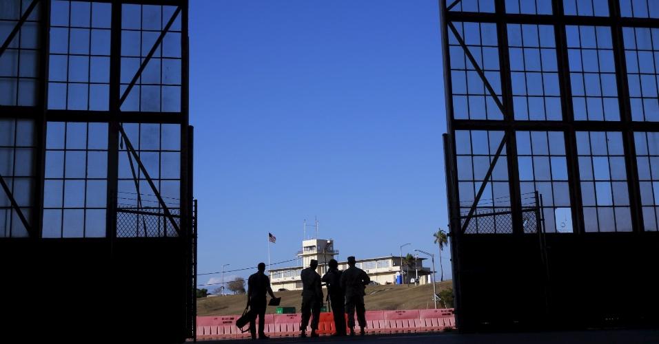 """28.mar.2016 - A base militar norte-americana em Guantánamo foi erguida anos após a vitória dos Estados Unidos na Guerra Hispano-Americana (1898), quando Cuba passou a viver sob forte influência americana. Mas, o território jamais foi considerado formalmente parte dos EUA e depois da Revolução Cubana, em 1959, Havana passou a exigir a devolução de Guantánamo, considerado um """"território ocupado ilegalmente"""". Na imagem, soldados e membros da imprensa conversam do lado de fora de um prédio da base Naval dos EUA, na baía de Guantánamo, em Cuba"""