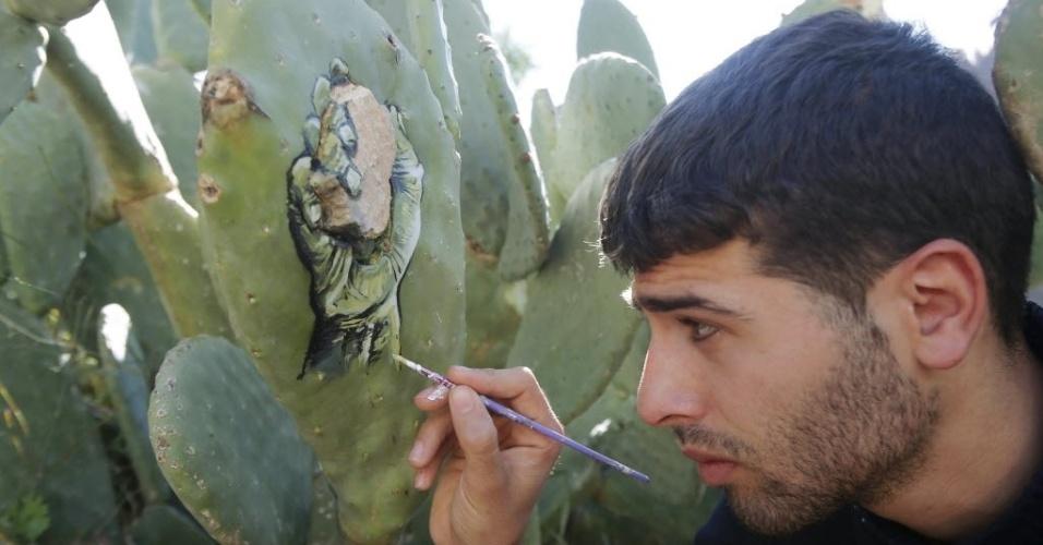 31.mar.2016 - O artista palestino Ahmad Yasin usa uma pedra que está cravada no cacto para criar uma pintura diferente no jardim de sua casa em Aseera Ashmaliya