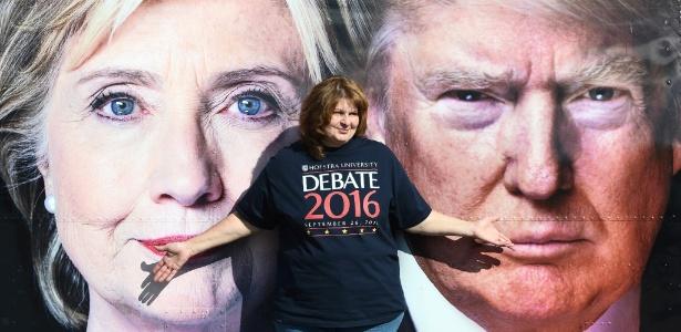 Mulher com camiseta oficial do primeiro debate presidencial posa diante da imagem de Hillary Clinton e Donald Trump, em Nova York