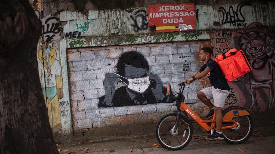 24.mar.2020 - Entregador passa por grafite do presidente Jair Bolsonaro (sem partido) usando uma máscara - Mauro Pimentel/AFP