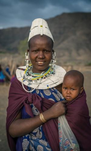 """12.jan.2016 - Mulher masai carrega seu bebê em imagem que faz parte do ensaio feito em outubro de 2015 pelo fotógrafo romeno Vlad Cioplea, durante expedição à Tanzânia. Ele passou 20 dias no país e registrou o cotidiano de três tribos locais: masai, bushman e tatoga. O fotógrafo conta que desejo de ir ao país africano surgiu após ver um documentário sobre a vida dos masai. """"Quando eu vi os masai eu soube que eu deveria ir para lá (Tanzânia) um dia"""", diz"""
