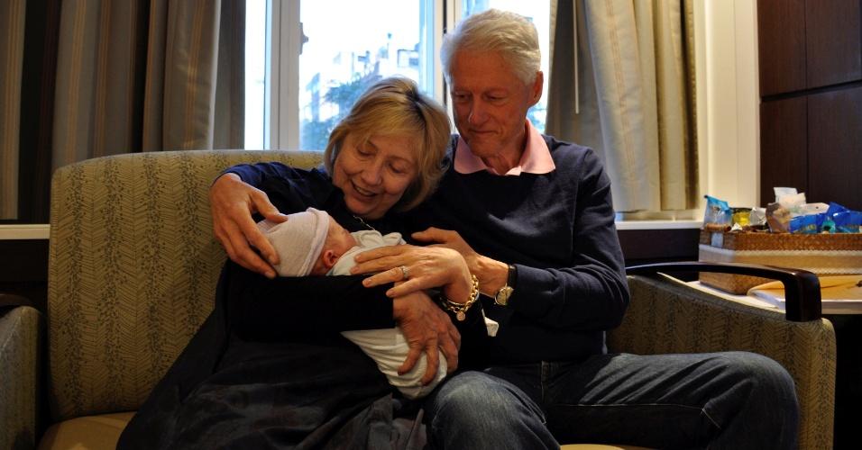 21.jun.2016 - A candidata democrata à Presidência dos EUA, Hillary Clinton, segura o neto recém-nascido no colo, ao lado do ex-presidente dos EUA Bill Clinton, seu marido. O bebê Aidan Clinton nasceu no sábado e é filho de Chelsea Clinton e Marc Mezvinsky