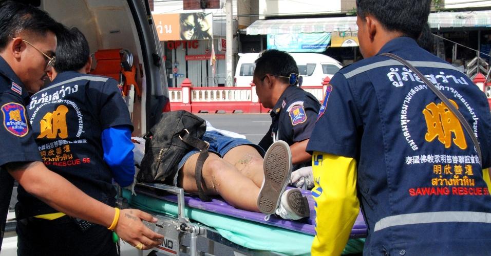 12.ago.2016 - Mulher é socorrida por equipe de emergência após explosão no enclave turístico de Hua Hin, a cerca de 150 km Bancoc. Entre a tarde de quinta (11) e a manhã desta sexta (12), pelo menos 12 artefatos explosivos foram detonados a distância em cinco cidades da Tailândia, deixando ao menos quatro tailandeses mortos e dez estrangeiros feridos