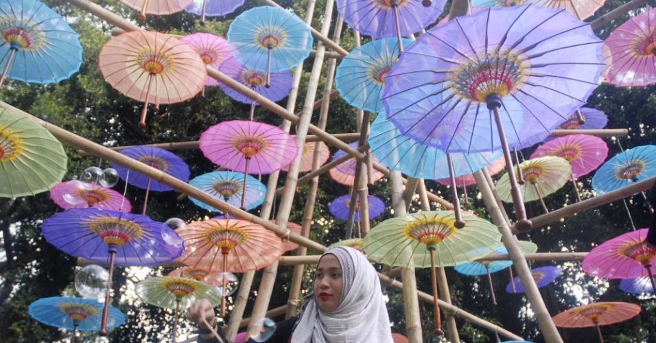 23.set.2016 - Mulher solta bolhas de sabão embaixo de guarda-chuvas durante o Festival Umbrella 2016, no Parque Balekambang em Solo, na província de Java Central, na Indonésia
