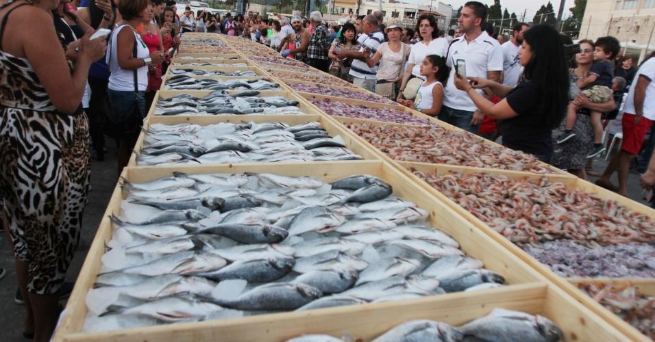 4.set.2016 - Pessoas se reúnem ao redor de peixes em Batroun, no Líbano. Um total de 2.613 kg de peixes foram exibidos, alcançando o recorde do Guinness pela maior mostra de alimentos do mar