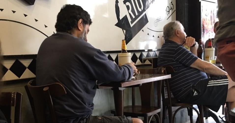 """6.nov.2016 - Carlos Humberto Gonçalves, 35, foi o único candidato do Enem (Exame Nacional do Ensino Médio) a chegar atrasado e reclamar do fechamento dos portões da PUC-Rio, na Gávea, na zona sul carioca. Segundo ele, três fatores foram preponderantes para que ele perdesse o segundo dia de prova do exame: o trânsito, os sinais fechados e a lentidão do motorista do ônibus. """"Saí de casa 12h10, achei que dava tempo"""", afirmou ele, que pretende cursar direito e mora em Copacabana, também na zona sul. Posteriormente, Gonçalves foi visto pela reportagem revisando anotações e bebendo uma cerveja no bar Simpatia, ao lado do Shopping da Gávea."""