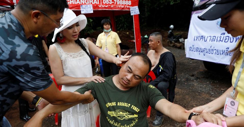 7.jul.2018 - Voluntários fazem massagem em soldado, após horas de trabalho, nas proximidades da caverna onde estão presos os 12 meninos e seu treinador