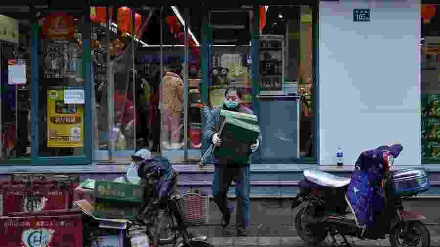 Moradores de Wuhan, epicentro do surto, só têm deixado suas casas para ir comprar mantimentos - HECTOR RETAMAL/AFP