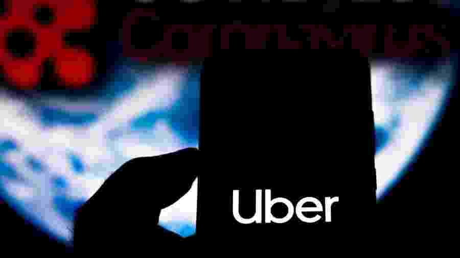 """5.abr.2020 - Foto ilustrativa mostra logo da Uber na tela de um celular em frente a uma tela onde se lê """"covid-19 - coronavírus"""" - Rafael Henrique/SOPA Images/LightRocket via Getty Images"""