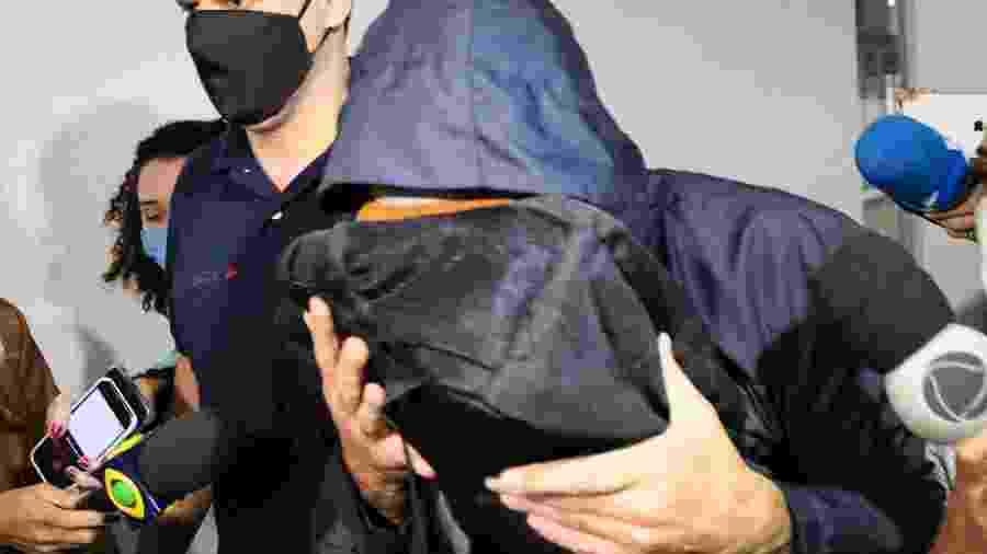 O ex-secretário estadual de Saúde do Rio, Edmar Santos (com o rosto coberto), é conduzido na chegada à Cidade da Polícia após ser preso - ANDRE MELO ANDRADE/MYPHOTO PRESS/ESTADÃO CONTEÚDO