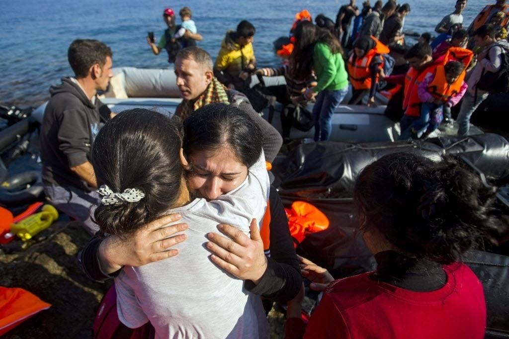 4.out.2015 - Refugiados vindos da Turquia comemoram chegada à Ilha de Lesbos, na Grécia. A terceira maior ilha grega já recebeu aproximadamente 90 mil refugiados vindos da Síria, Afeganistão e Iraque que tentam chegar à Europa fugindo de guerras