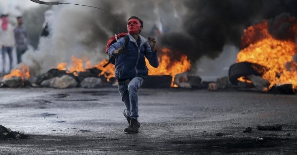 26.out.2015 - Um manifestante palestino usa um estilingue para arremessar pedras em direção a tropas israelenses perto do assentamento judaico de Bet El, na Cisjordânia. O primeiro-ministro de israelense, Benjamin Netanyahu, avalia revogar a permissão de residência de palestinos em bairros de Jerusalém Oriental