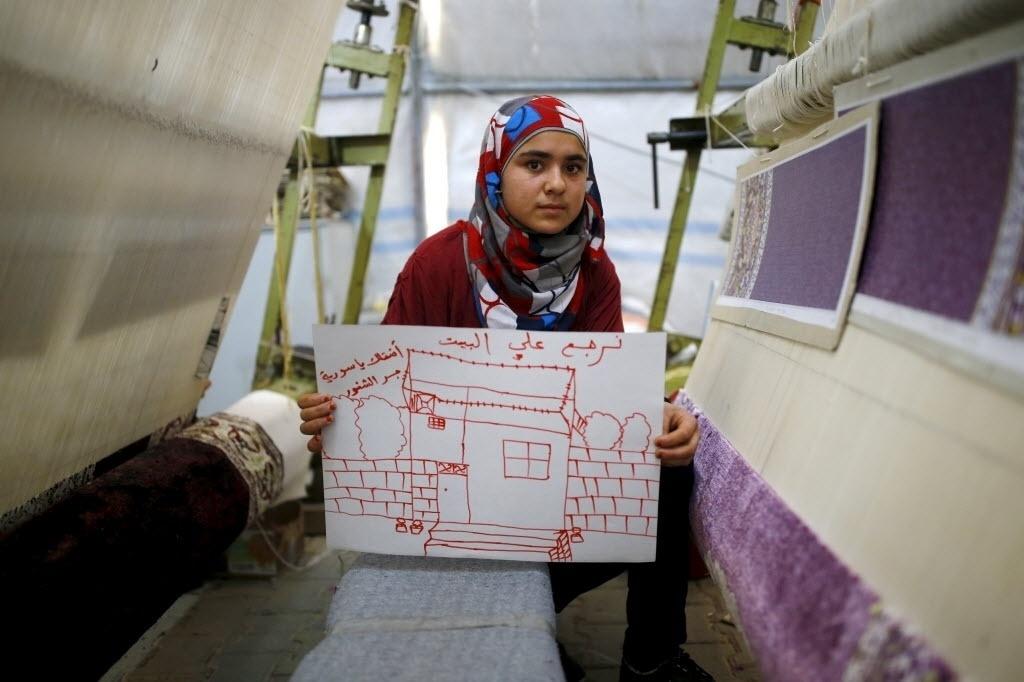 A refugiada síria Meryem Mahmo,14, mostra desenho de sua casa na Síria, durante uma oficina de tecelagem de tapetes no campo de refugiados de Midyat, na província de Mardin, Turquia. Na escrita em árabe lê-se: