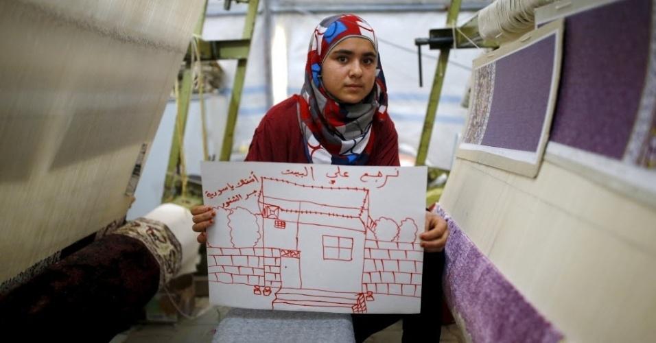 """A refugiada síria Meryem Mahmo,14, mostra desenho de sua casa na Síria, durante uma oficina de tecelagem de tapetes no campo de refugiados de Midyat, na província de Mardin, Turquia. Na escrita em árabe lê-se: """"Eu quero minha casa. Eu sinto sua falta, Síria"""". A guerra civil na Síria, que já deixou centenas de milhares de mortos, empurra outros tantos para o exílio, entre muitos deles crianças. Os desenhos das crianças do acampamento mostram memórias de suas casas, traumas vividos e esperanças para o seu futuro. Dos 2,3 milhões de refugiados sírios que vivem na Turquia, mais da metade são crianças"""