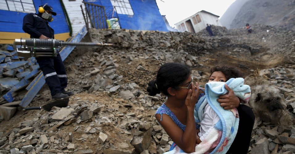 1º.fev.2016 - Uma mãe e um bebê se protegem enquanto um funcionário realiza o combate a mosquitos em um distrito nas redondezas de Lima, no Peru. A OMS (Organização Mundial de Saúde) decretou emergência mundial contra o vírus zika, transmitido pelo mosquito 'Aedes aegypti'