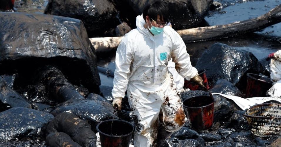 29.mar.2016 -Trabalhador carrega baldes de petróleo que vazaram de um navio de carga à beira-mar em Nova Taipé, Taiwan. O navio transportava 447 toneladas de combustível quando encalhou na semana passada