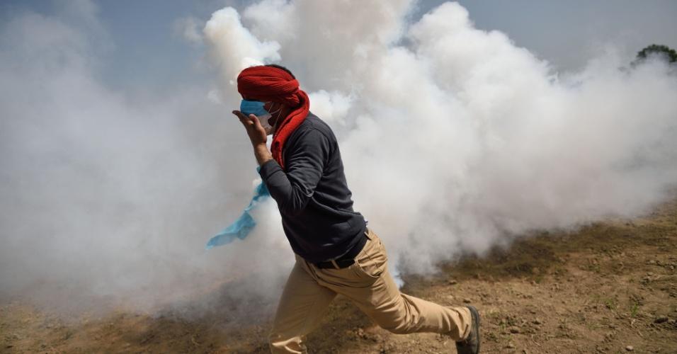 13.abr.2016 - Refugiado na vila grega de Idomeni corre de gás lacrimogêneo jogado por policiais da Macedônia. O confronto começou quando imigrantes no lado grego se aproximaram da cerca de arame farpado que separa a fronteira dos dois países  e começaram a sacudi-la