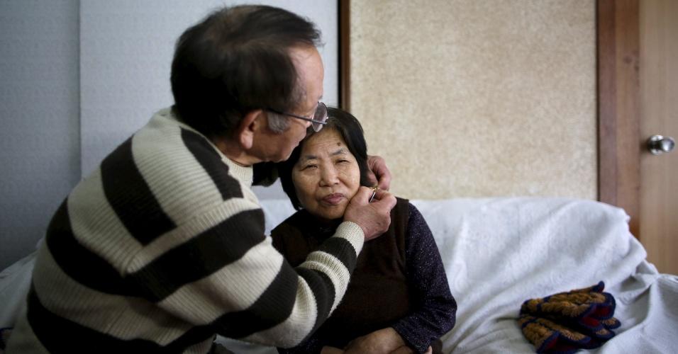 18.abr.2016 - Kanemasa Ito coloca um colar com um GPS na mulher, Kimiko, 68, que foi diagnosticada com demência há 11 anos. Grande parte dos pacientes que sofrem algum tipo de demência no Japão vivem com familiares, que lutam para conciliar o cuidado com os trabalhos, mas a cada ano cerca de 100 mil pessoas acabam deixando de trabalhar para desempenhar a tarefa