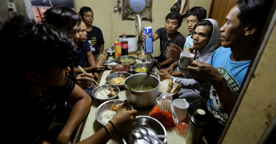 4.jul.2016 - Pescadores do Suriname e Indonésia se sentam à mesa para comer o iftar dentro de uma embarcação no rio Suriname, em Livorno (Suriname)