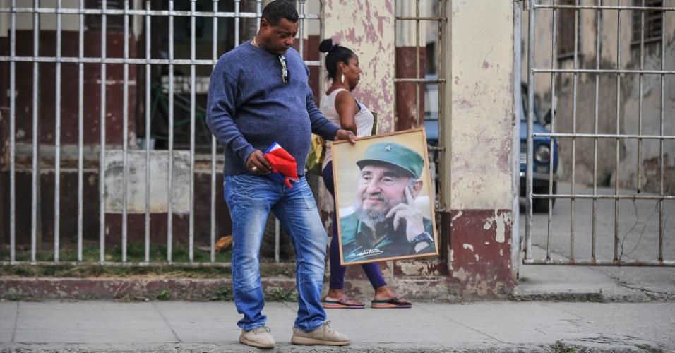 27.nov.2016 - Dois dias depois da morte de Fidel Castro, um homem segura uma bandeira de Cuba e um quadro com a foto do ex-presidente, em Havana