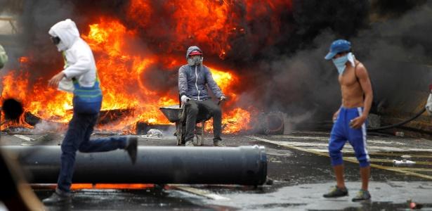 Manifestantes fazem barricada de fogo durante protesto contra Nicolás Maduro em Caracas - Christian Veron/Reuters
