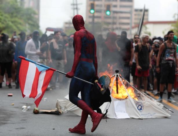Homem vestido de Homem-Aranha passa por barricada durante protesto contra medidas de austeridades impostas pelo governo de Porto Rico, em San Juan