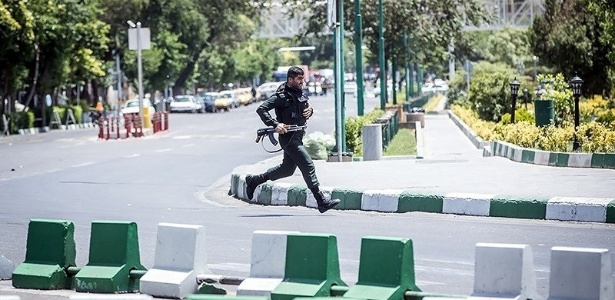 Integrante das forças de segurança do Irã corre durante ataque ao Parlamento, em Teerã