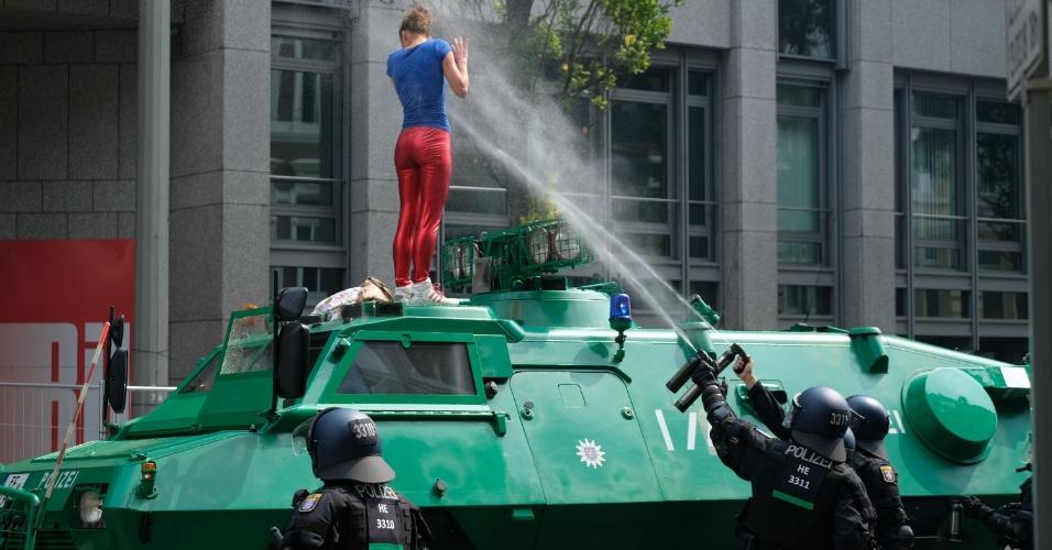 7.jul.2017 - Policiais lançam spray de pimenta em manifestante que subiu em veículo policial durante protesto em Hamburgo, Alemanha
