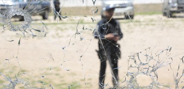 6.jul.2017 - Policial é visto através de vidro de janela atingida por balas após conflito entre grupos armados, México