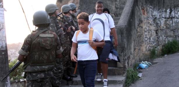 Crianças cruzam com soldados em patrulha na favela da Rocinha, no RJ (27.out.2017)