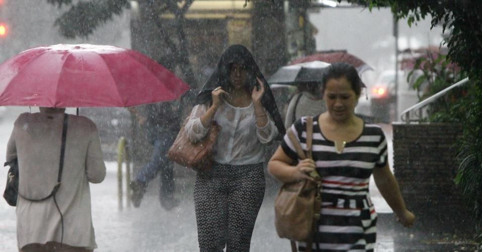 28.mar.2018 - Pedestres enfrentam forte chuva na Avenida Paulista, região central de São Paulo, na tarde desta quarta-feira, 28.