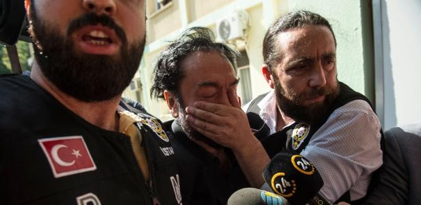 Policial turco cobre a boca de líder criacionista Adnan Oktar ao escoltá-lo para a cadeia em Istambul sob a acusação de cometer fraudes - Dogan News Agency/AFP