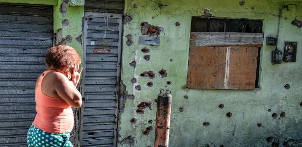 Mulher passa em frente a casa cheia de buracos de balas no Complexo do Alemão (RJ) - 25.abr.2017 - Fabio Teixeira/AFP