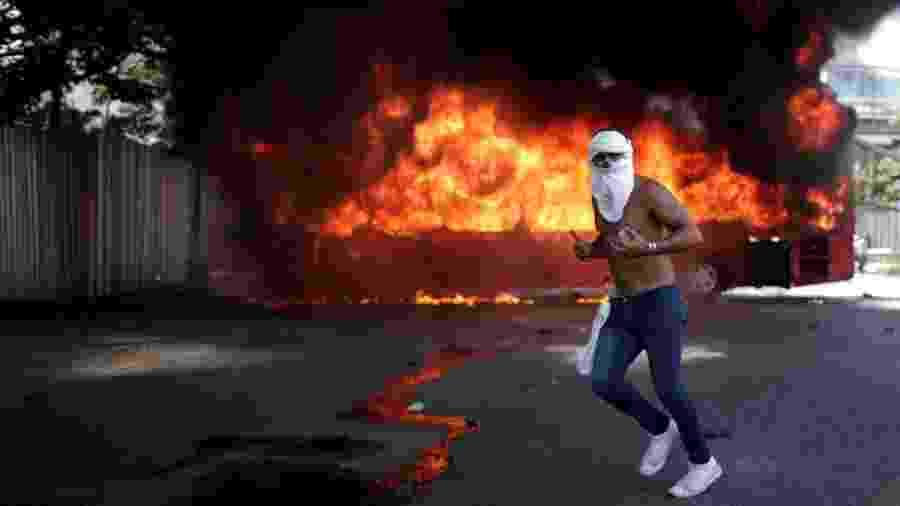 """30.abr.2019 - Manifestante opositor a Nicolás Maduro segura uma pedra em frente a um ônibus em chamas na região da base aérea """"La Carlota"""", em Caracas, na Venezuela - Ueslei Marcelino/Reuters"""