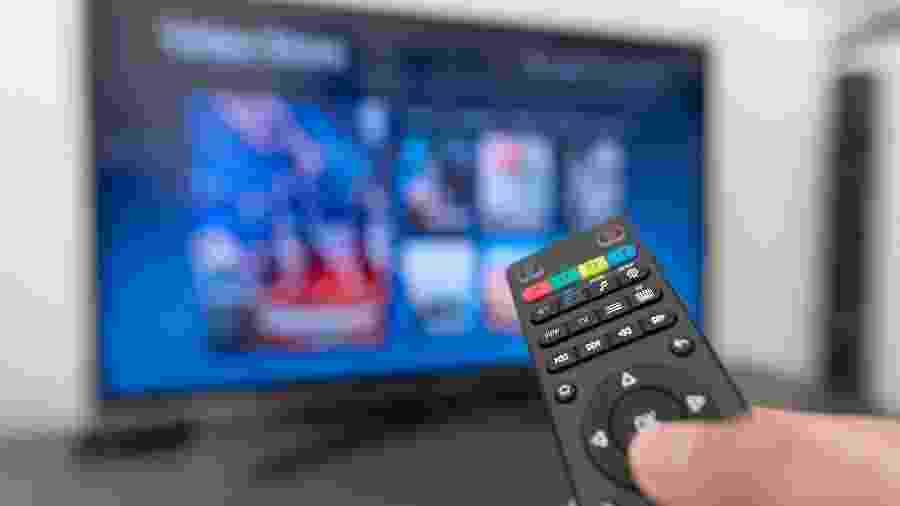 Controle diante de um televisor sintonizada em um serviço de TV paga - Getty Images/iStockphoto