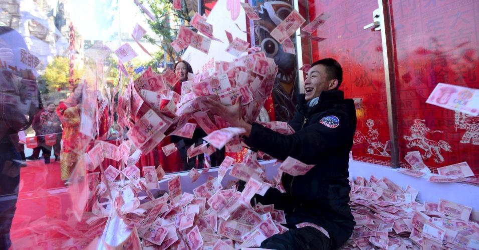 27.jan.2016 - Um homem tenta agarrar cédulas de 100 yuan dentro de uma caixa de vidro durante celebração da chegada do Festival da Primavera, em um parque em Hangzhou, na província de Zhejiang (China). Dentro da caixa havia 5 milhões de yuan (cerca de R$ 3 milhões). Dez pessoas foram colocadas dentro dela e podiam levar quanto pudessem pegar em um minuto. Um dos visitantes ganhou 18,3 mil yuans (cerca de R$ 11,3 mil)