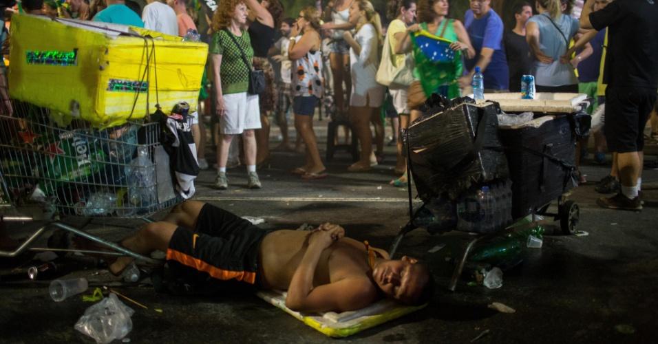 17.abr.2016 - Vendedor ambulante dorme na avenida Atlântica, na praia de Copacabana, enquanto manifestantes comemoram a aprovação do processo de impeachment da presidente Dilma Rousseff. Protestos contra e a favor do atual governo foram realizados em Copacabana, na zona sul do Rio de Janeiro
