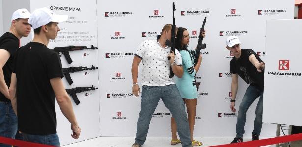 Casal posa para foto com rifles Kalashnikov em uma mostra promocional em Moscou (Rússia)