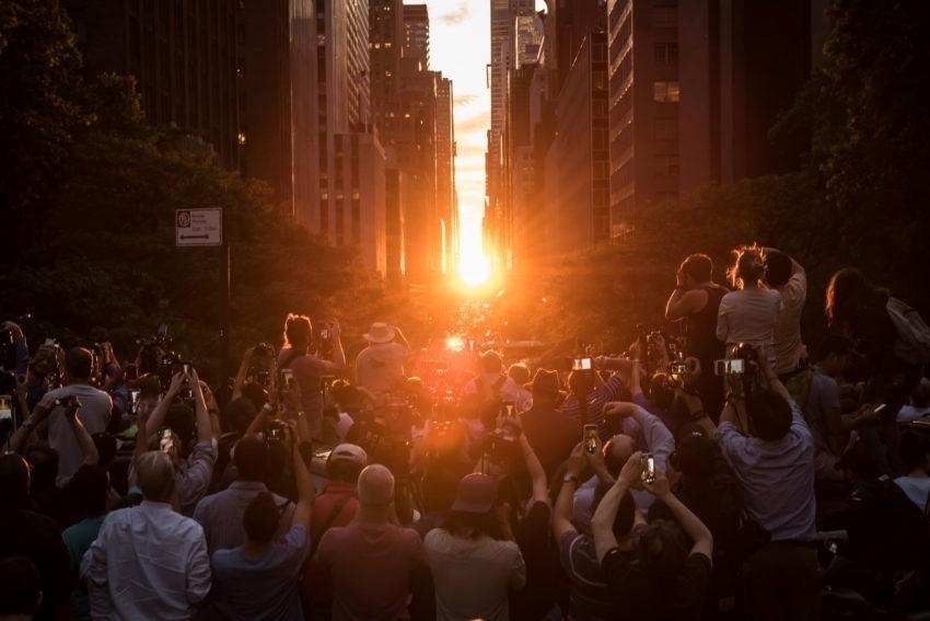 12.jul.2016 - Multidão se aglomera para tirar fotos do sol durante o 'Manhattanhenge', como é conhecido o fenômeno do alinhamento do sol aos prédios de Nova York (EUA). Isso acontece duas vezes por ano