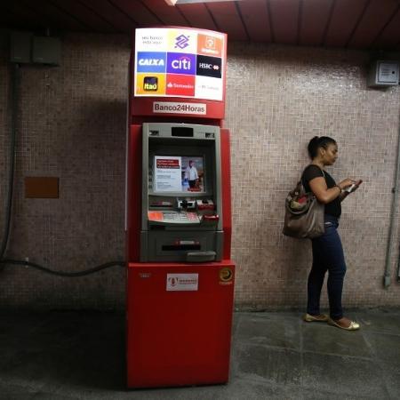 Mulher utiliza o celular ao lado de caixa eletrônico no Rio de Janeiro - PILAR OLIVARES